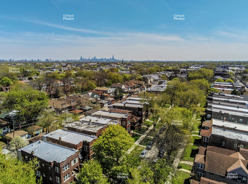 Aerial drone view above residential streets of Albany Park neighborhood with skyline in the distance.
