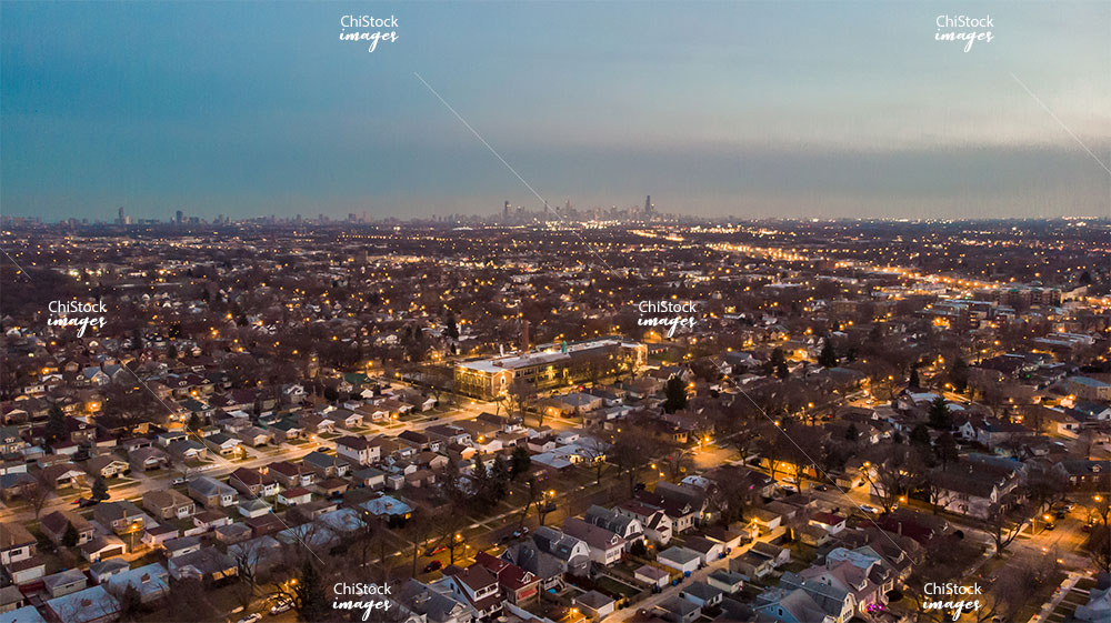 Night aerial drone view above residential streets of Albany Park neighborhood with skyline in the distance